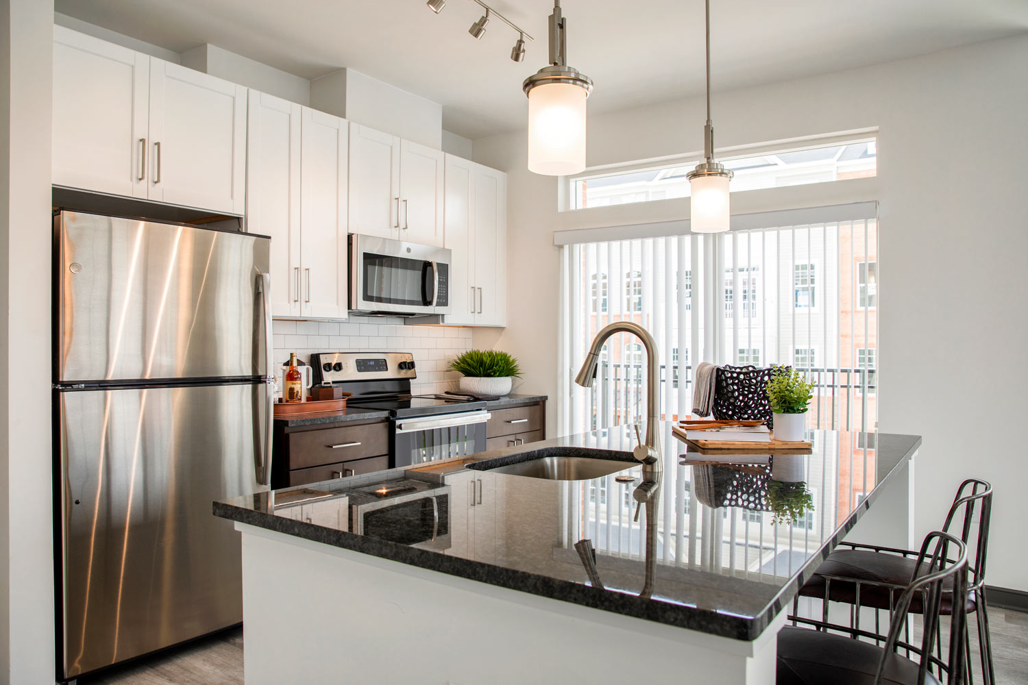 kitchen at Dartmoor Place at Oxford Square apartments in Hanover MD with stainless steel appliances, white cabinets and a black marble counter top and island
