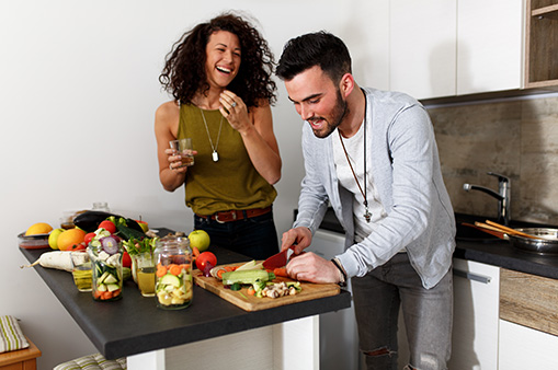 man and woman prepping vegetables for cooking in kitchen while laughing