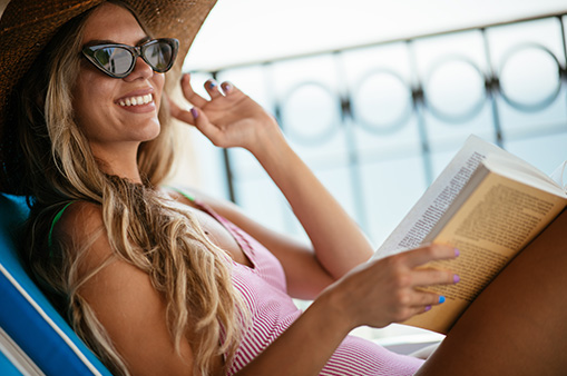 smiling woman in pink bathing suit, sunglasses and sunhat sitting in lounge chair reading a book