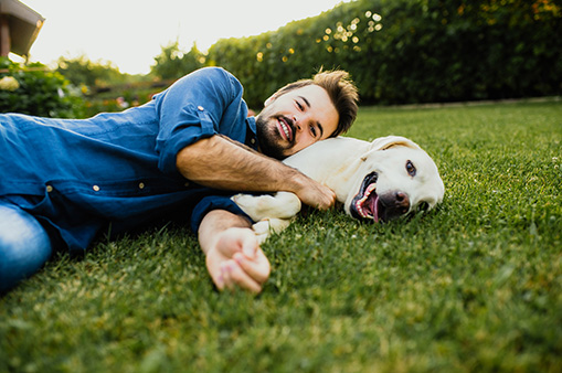 man in blue shirt smiling at camera while lying down with dog in the grass