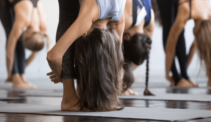 women in yoga class in same yoga pose facing down | Dartmoor Place